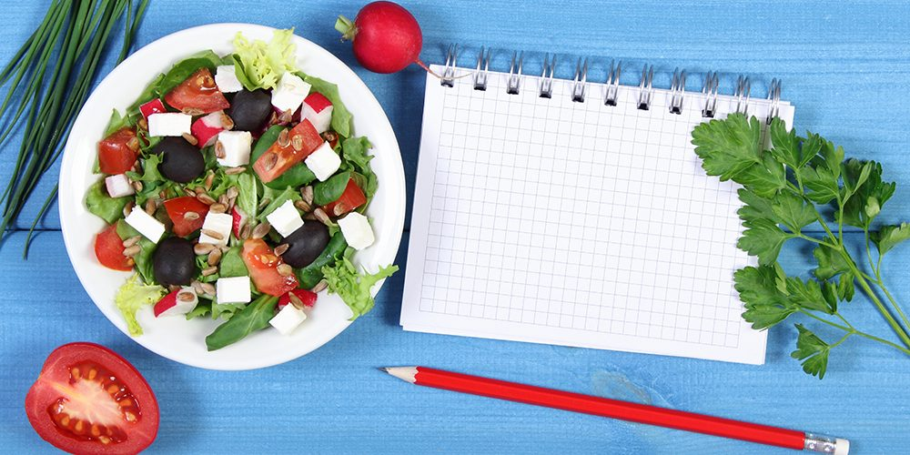 Fresh greek salad with vegetables and notepad for writing notes, concept of healthy lifestyle, slimming and nutrition